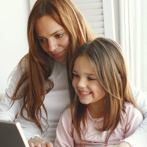 Little girl looking at laptop with her mother.  Woman in a white sweater. Enjoying spending time together.